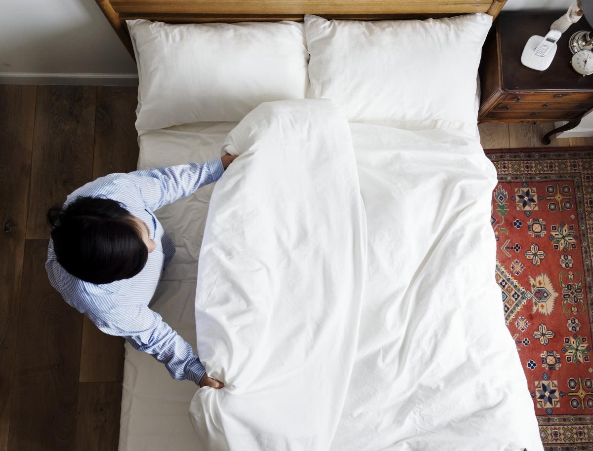 專業暖床員正在整理好剛剛暖好的床